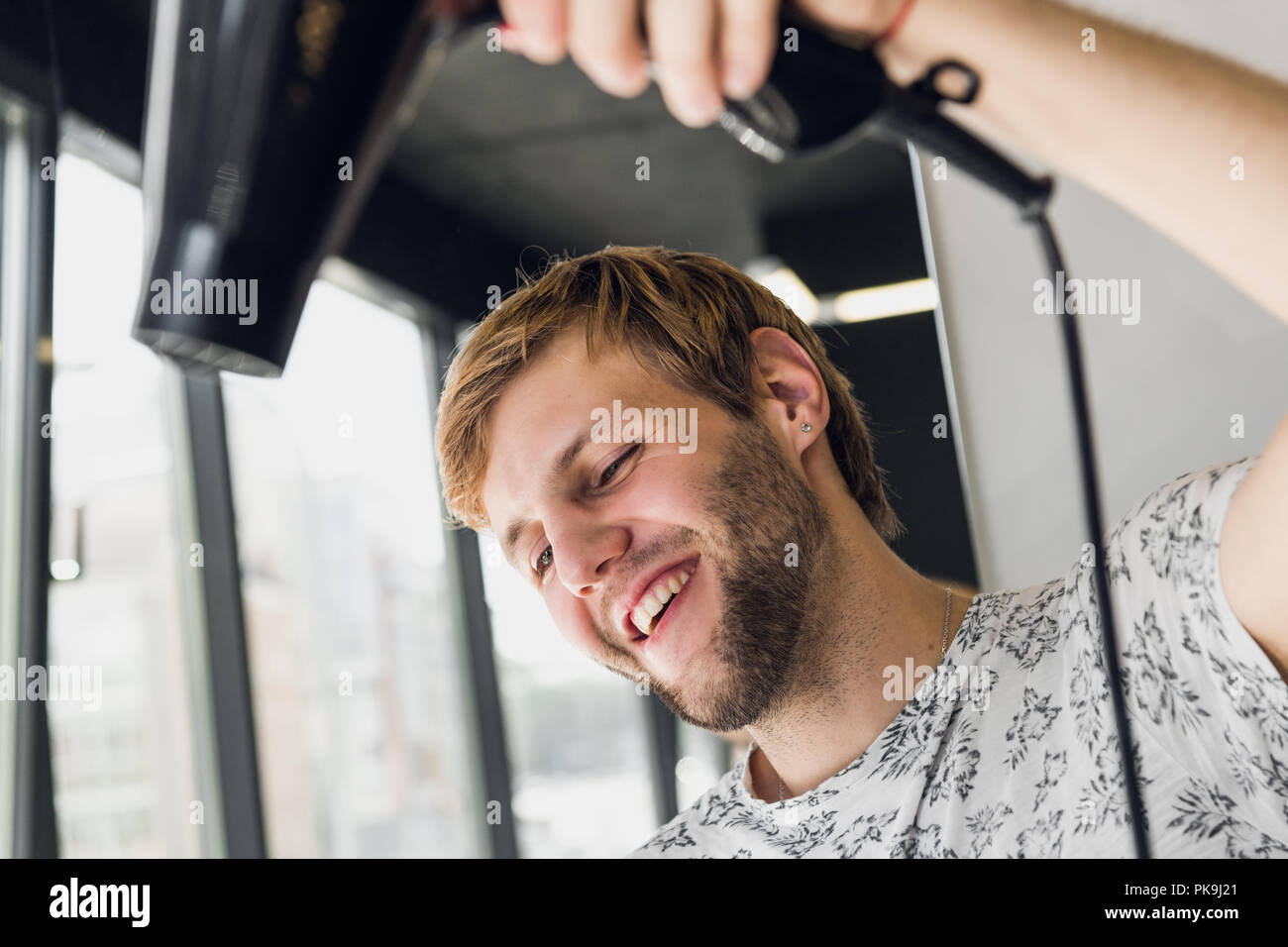 Portrait of happy hairdresser holding comb and blow dryer in salon - Stock Image