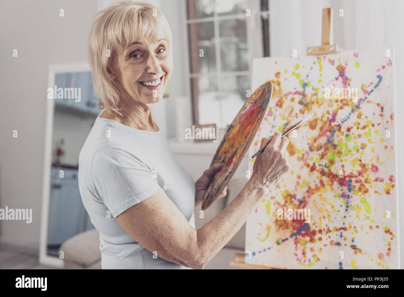 Smiling woman with facial wrinkles working with painting brush - Stock Image