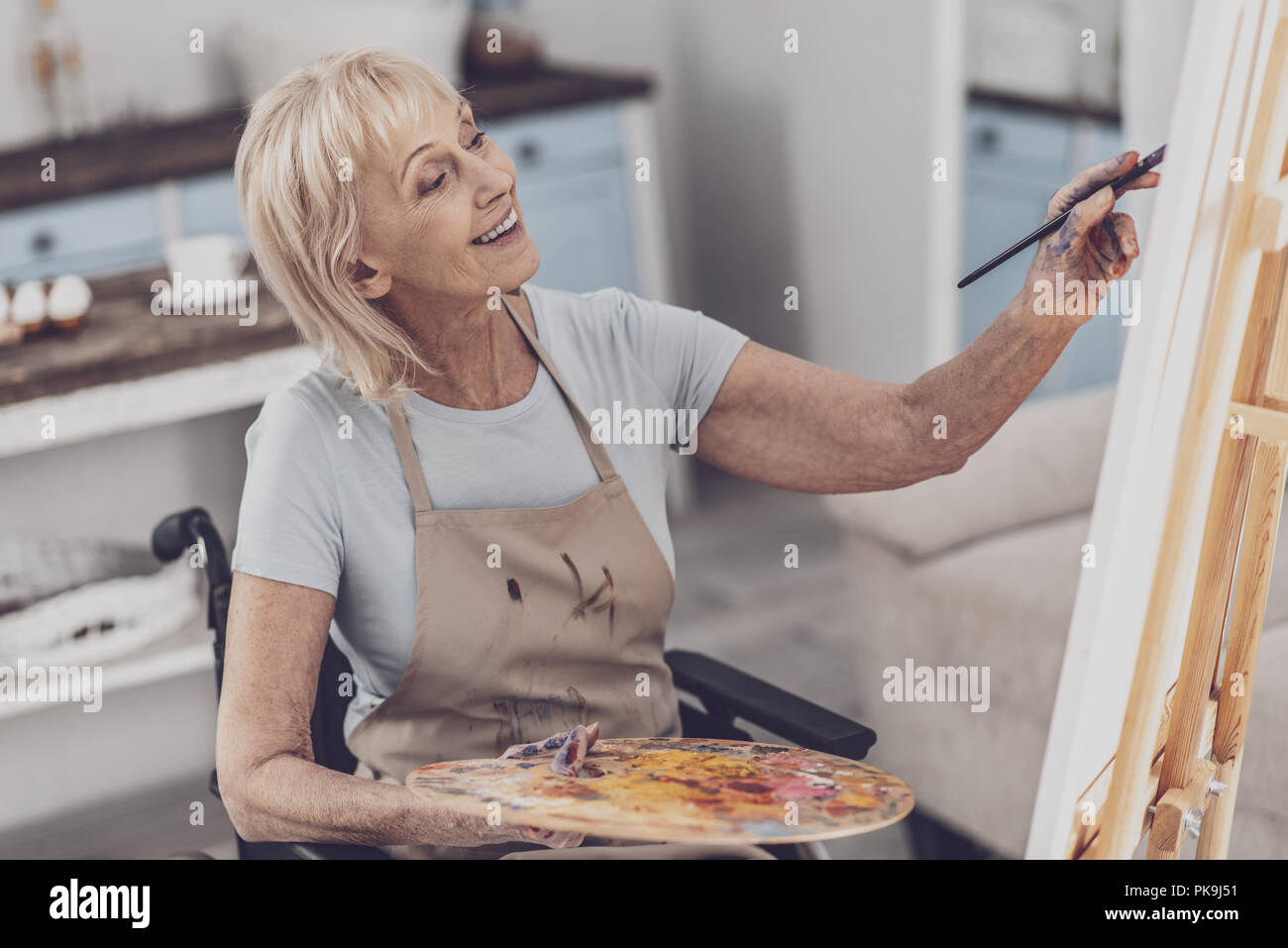 Creative disabled woman enjoying process of drawing - Stock Image