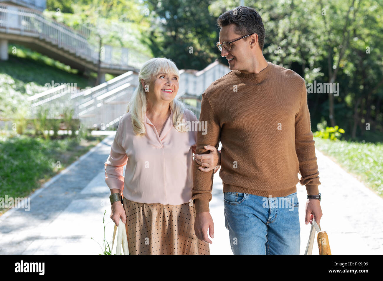 Kind male person helping his mature mother - Stock Image