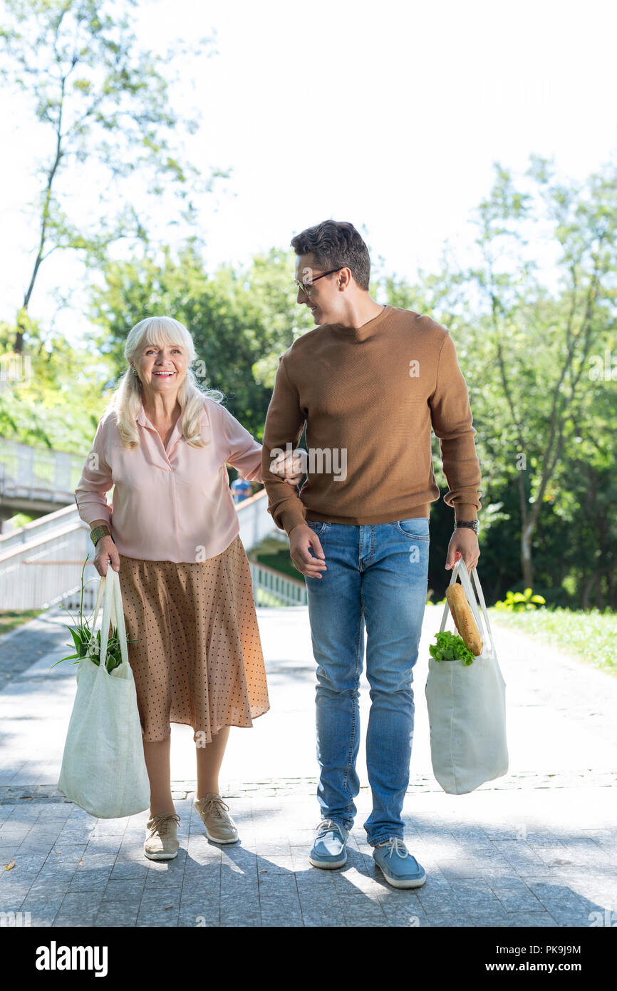 Positive delighted retired female walking in park - Stock Image