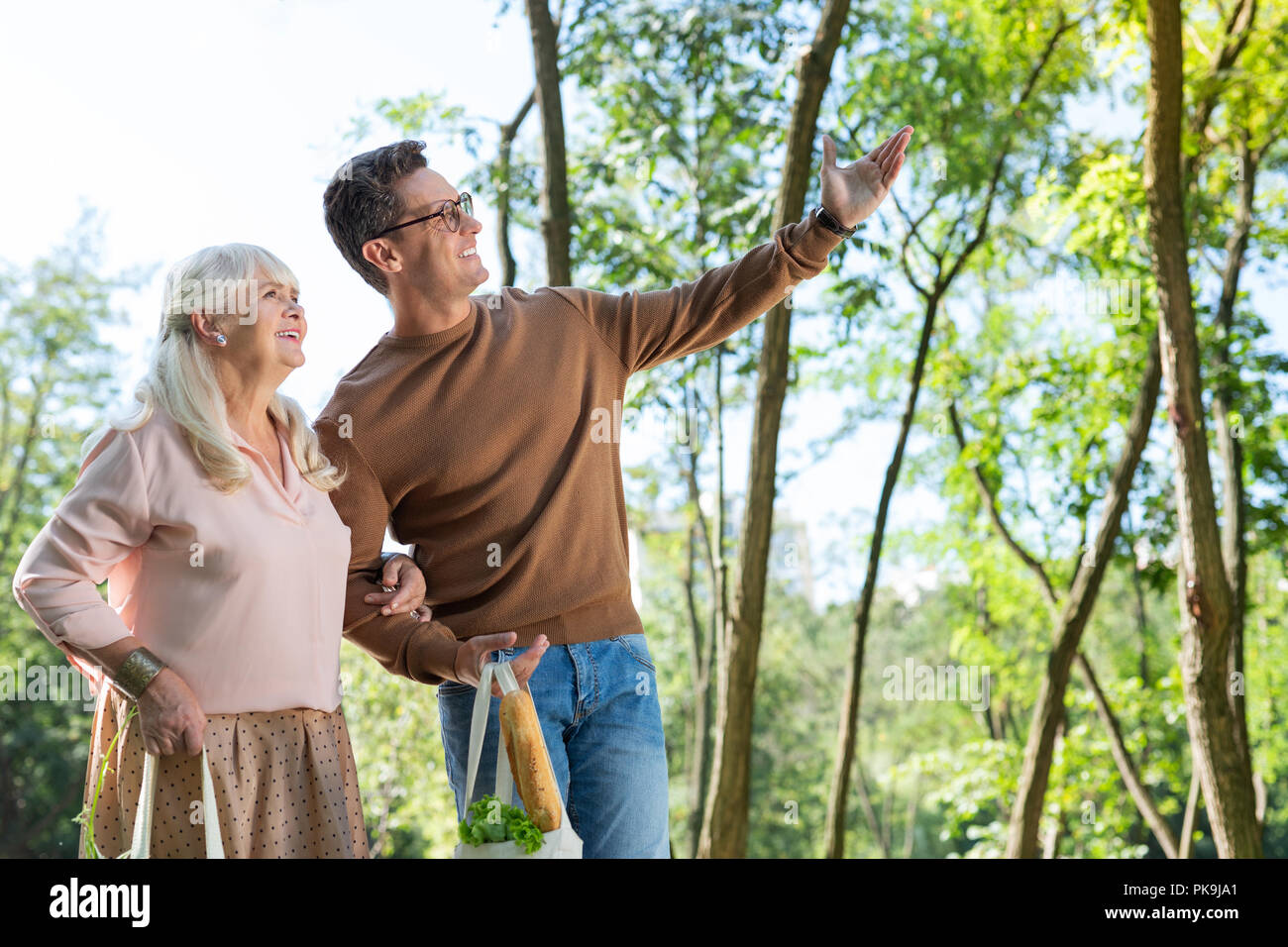 Delighted mature woman leaning on her helper - Stock Image