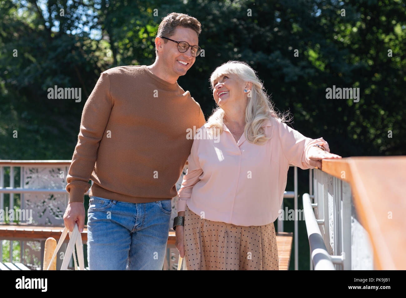 Handsome young male person supporting elderly woman - Stock Image