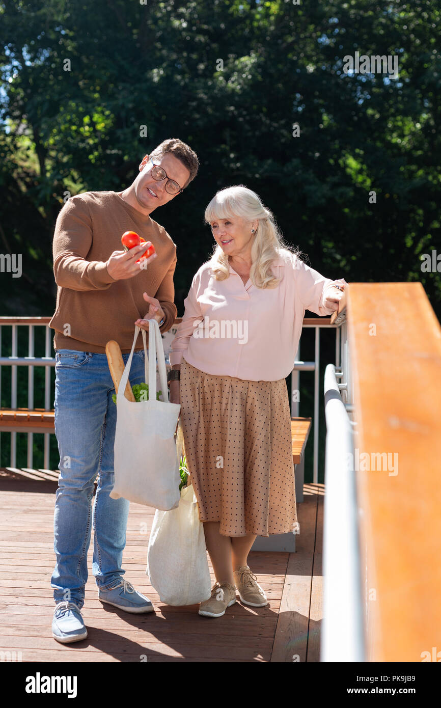 Delighted people having break while walking in park - Stock Image