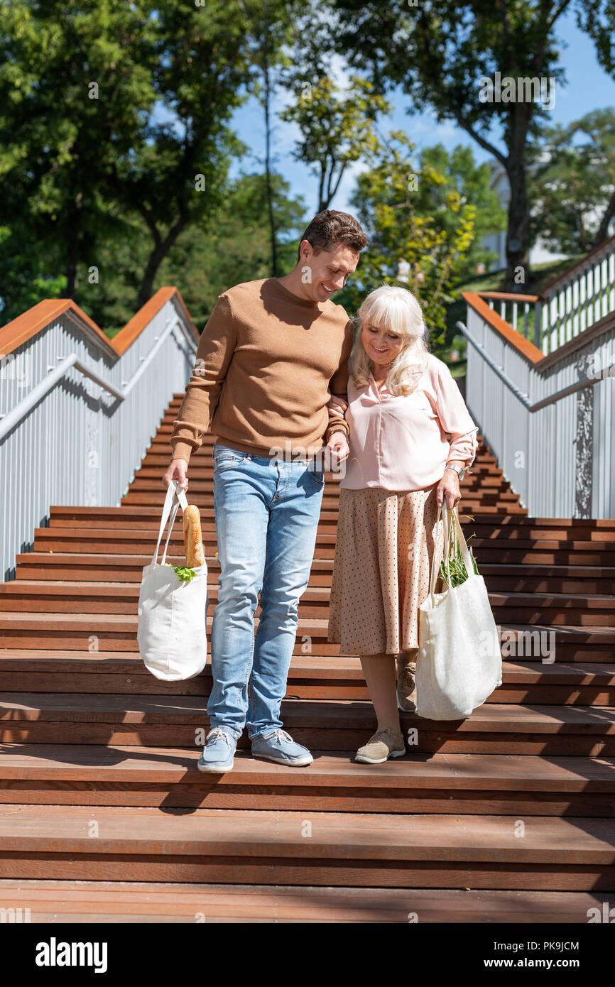 Beautiful mature woman walking with young man - Stock Image