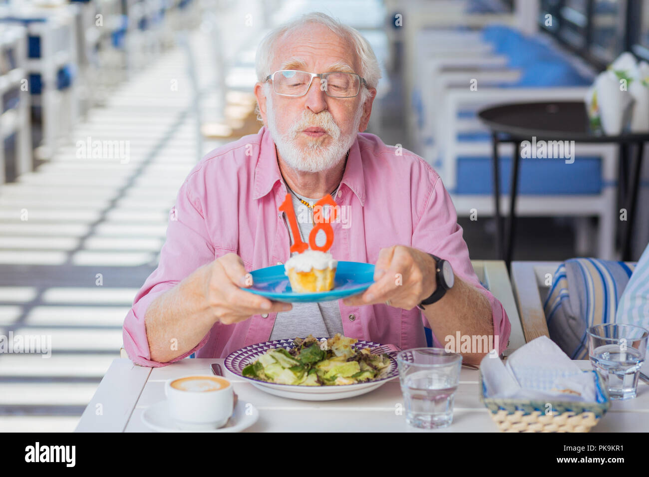 Positive aged man having a birthday party - Stock Image