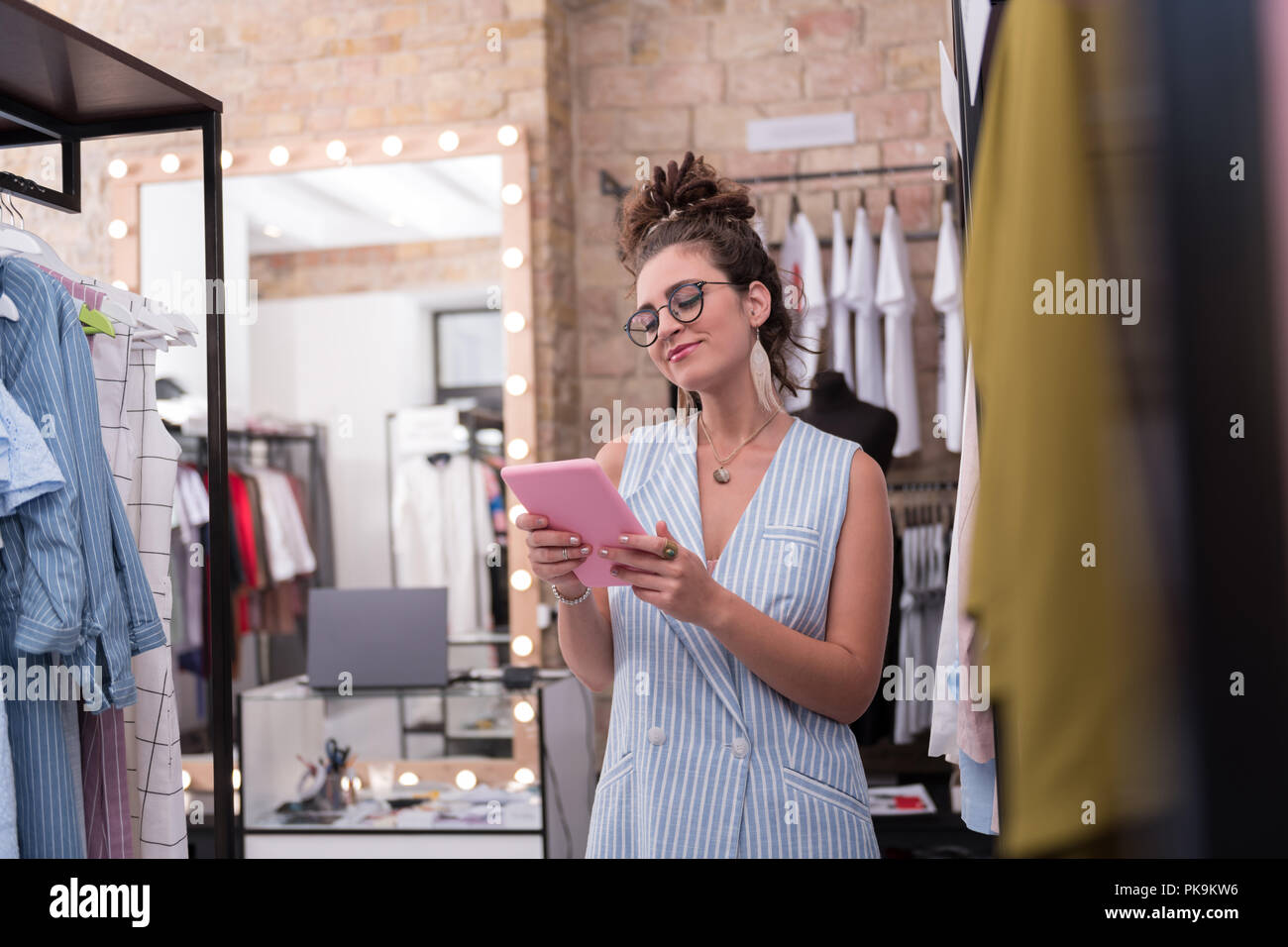 Glad female shop assistant checking available sizes - Stock Image