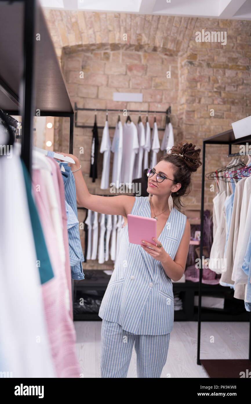 Jolly female shop assistant controlling clothes sizes - Stock Image