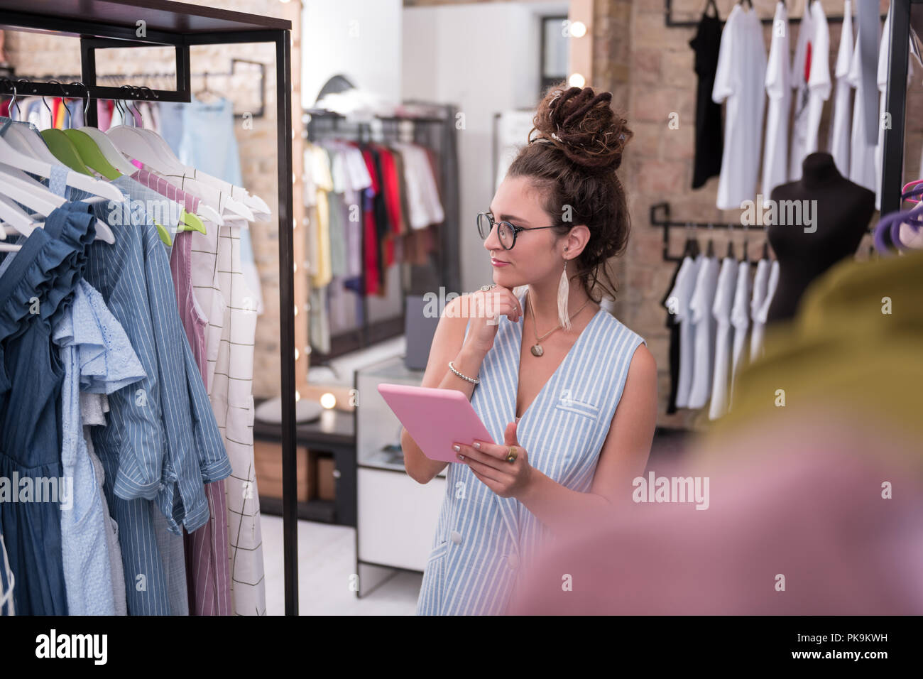 Reflective female shop assistant studying new arrivals - Stock Image