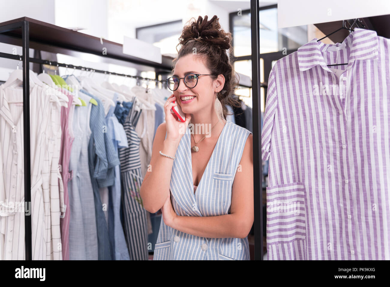 Cheerful female showroom owner talking on phone - Stock Image
