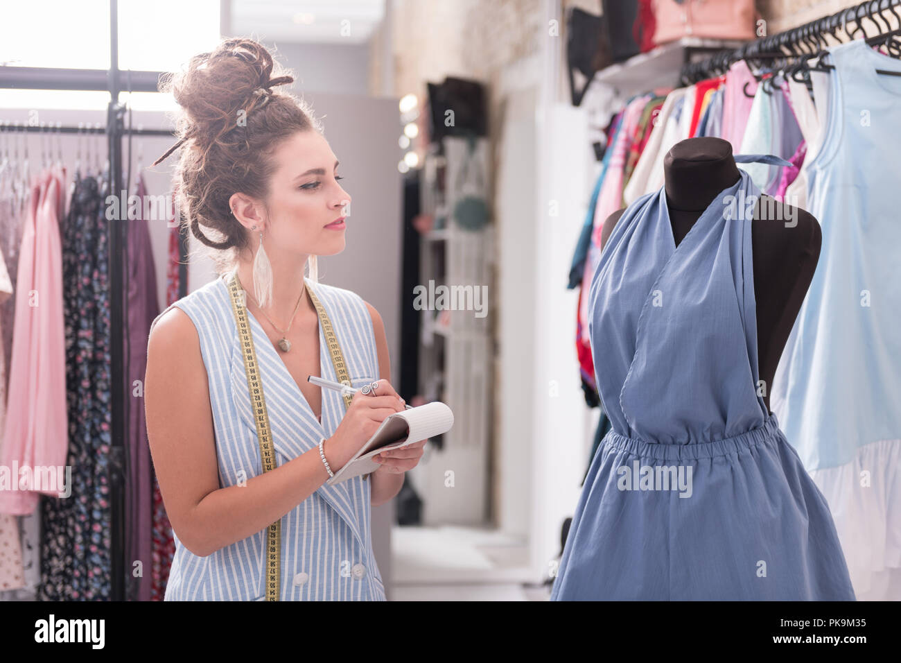 Dreamful female designer noting measurements in atelier - Stock Image