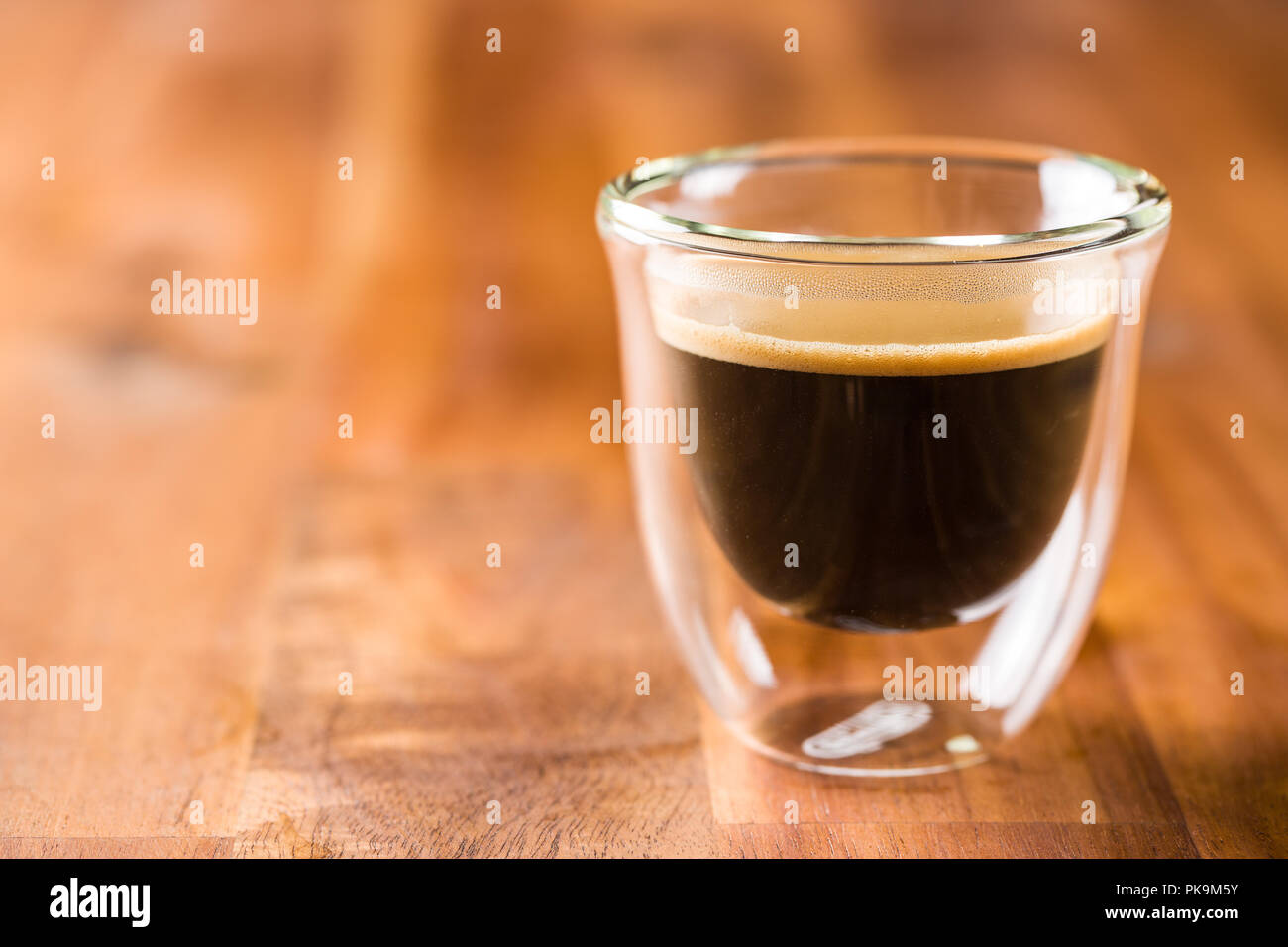 Cup of espresso coffee on wooden table. - Stock Image