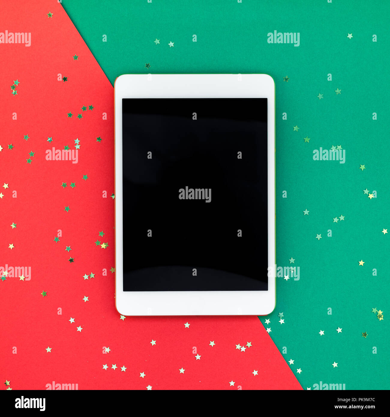 creative new year or christmas tablet pc mockup flat lay top view xmas holiday celebration mobile device ipad on red green paper background template