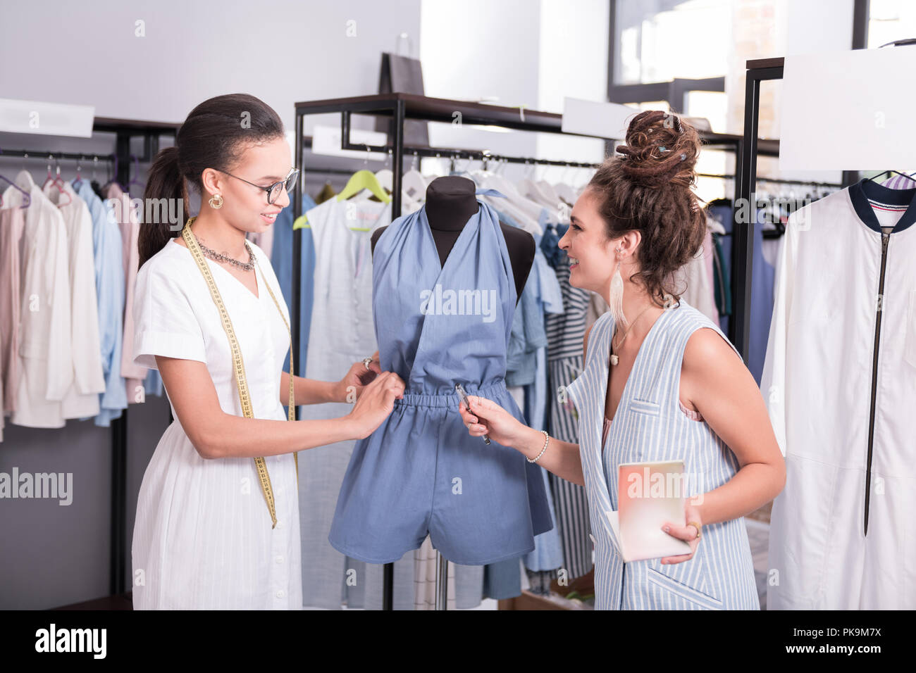 Merry two designers discussing overalls in showroom - Stock Image