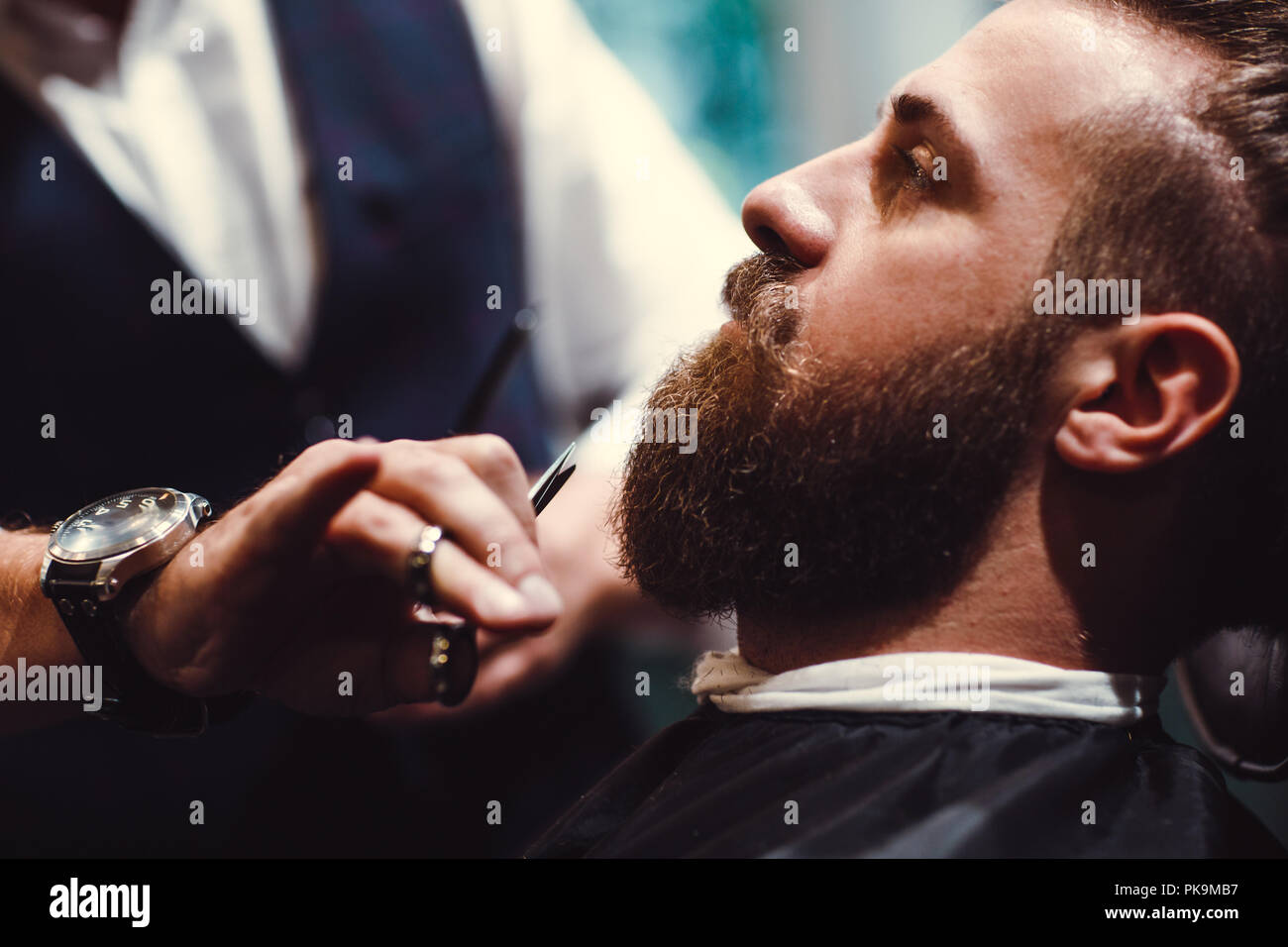 Barbershop with wooden interior. Bearded model man and barber. - Stock Image