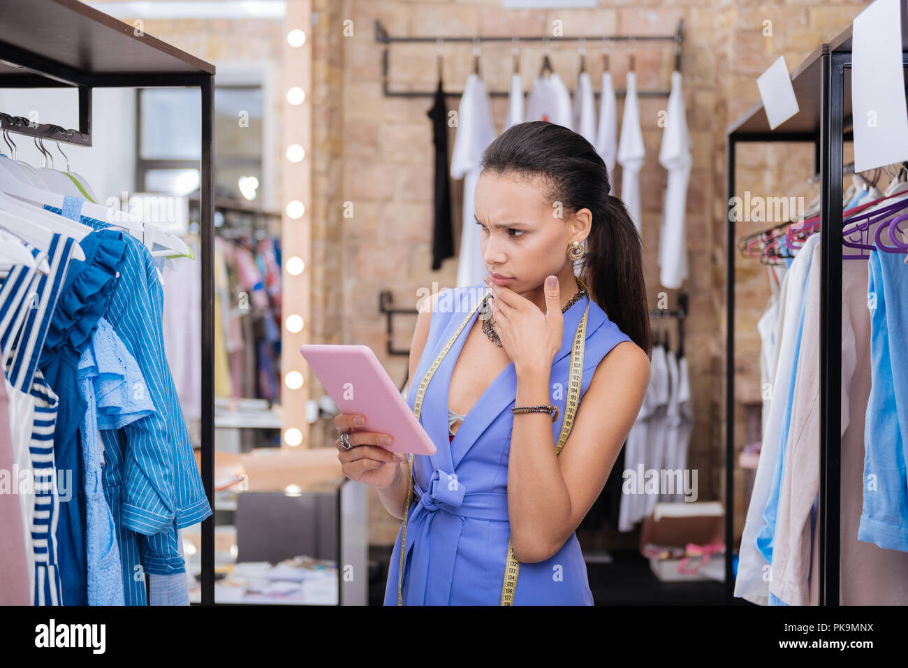 Concerned female sale assistant checking product representation - Stock Image