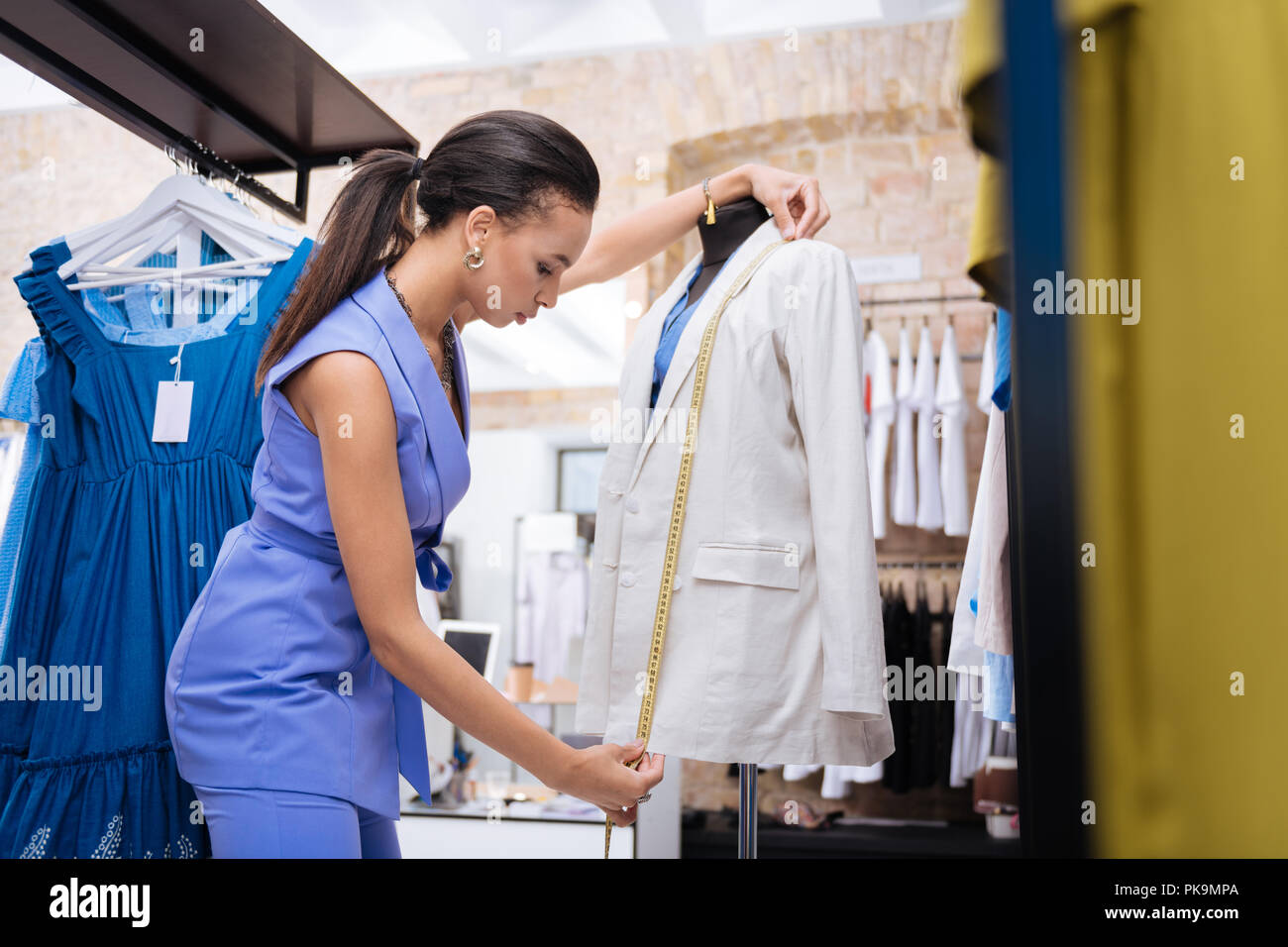 Focused female sale assistant measuring jacket length - Stock Image