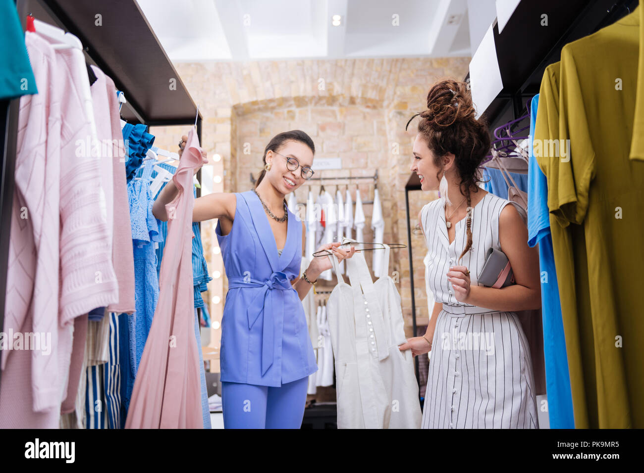 Merry female stylist offering outfit to woman - Stock Image