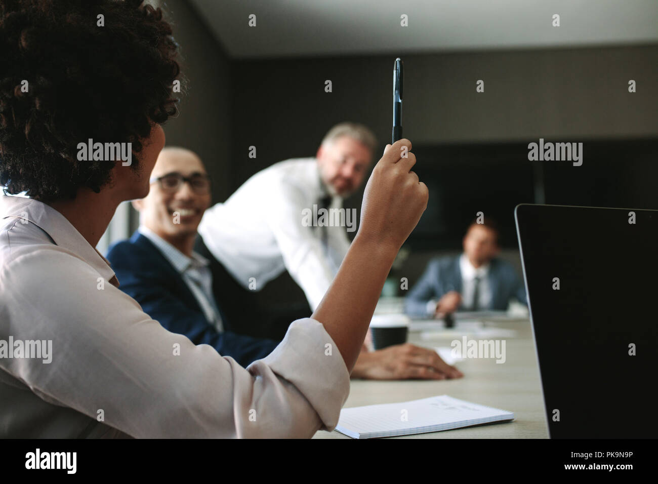 Woman asking a query to the team during a meeting. Business people having a meeting in board room. - Stock Image