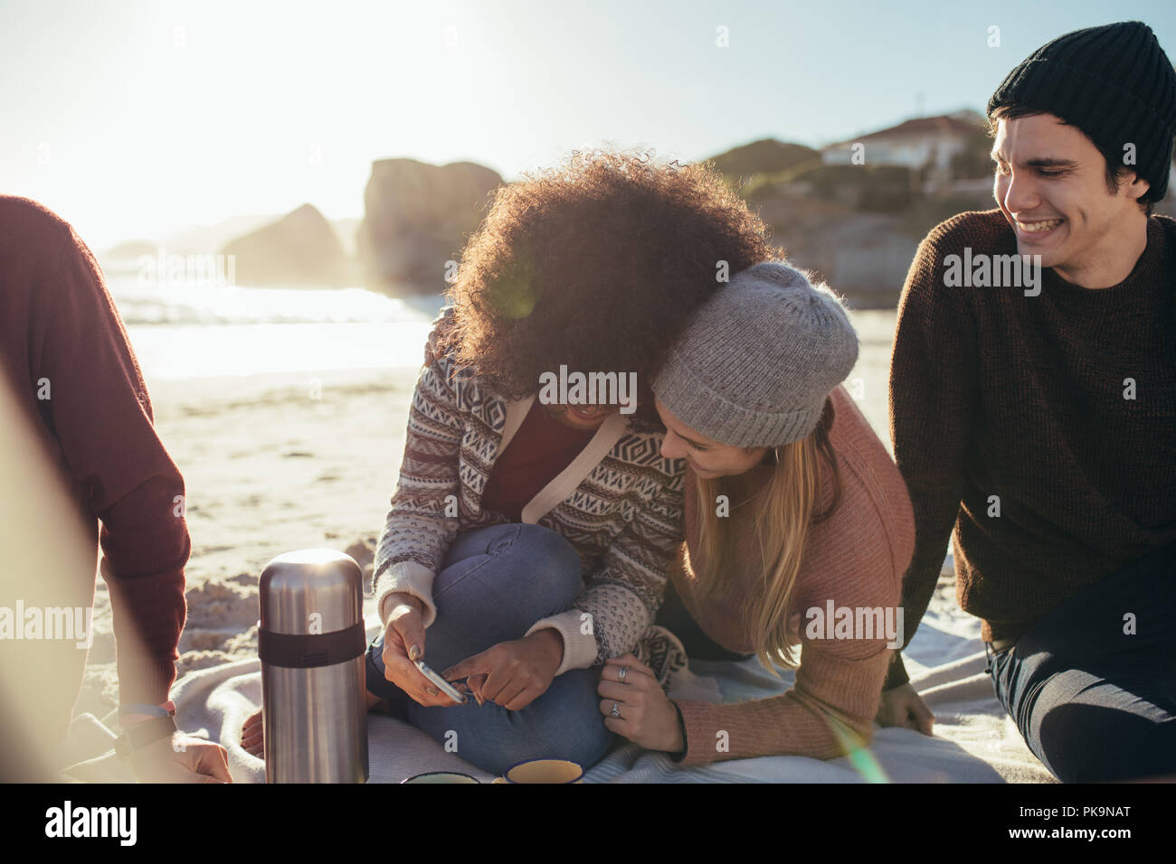 Two young woman sitting on the beach looking something funny on mobile phone and smiling with a friends sitting by. Group of young people relaxing on  Stock Photo