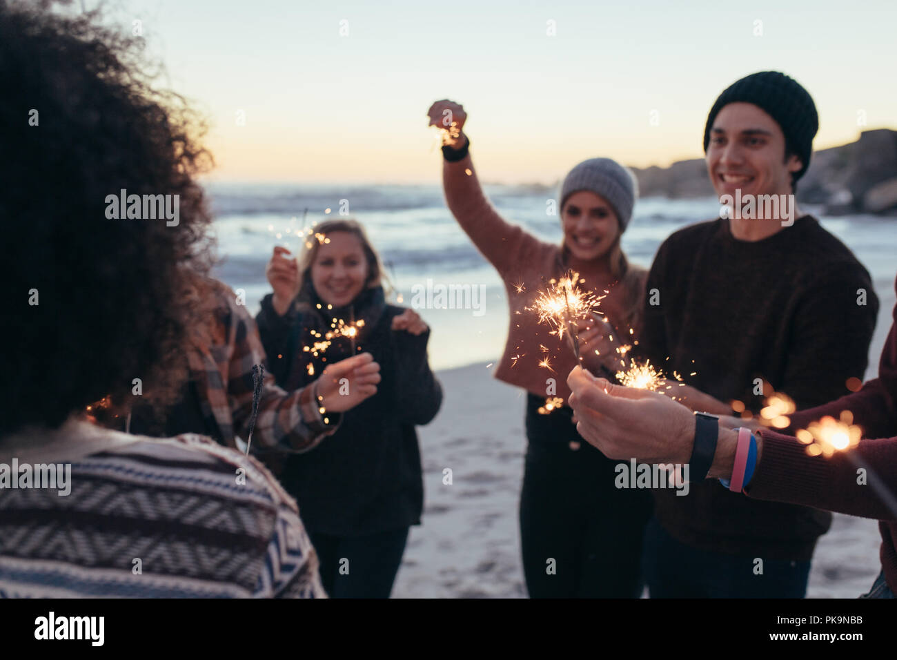 Diverse group of young people celebrating new year's day at the beach. Young people having fun with sparklers outdoors at the sea shore. - Stock Image