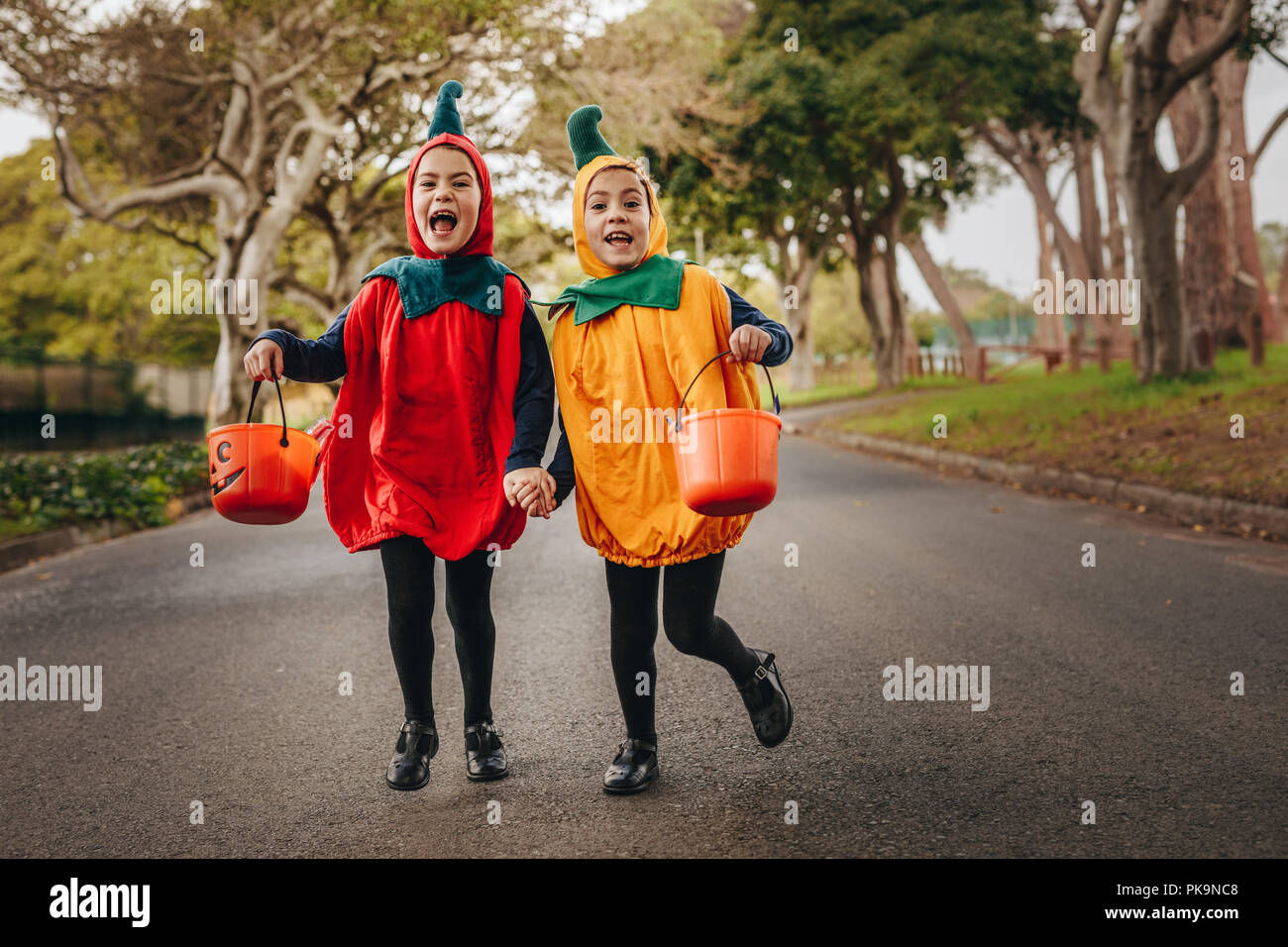 cute little girls in halloween costume trick or treating outdoors