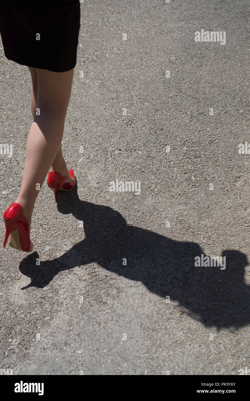 Rear view close up of a woman wearing red shoes running away Stock Photo