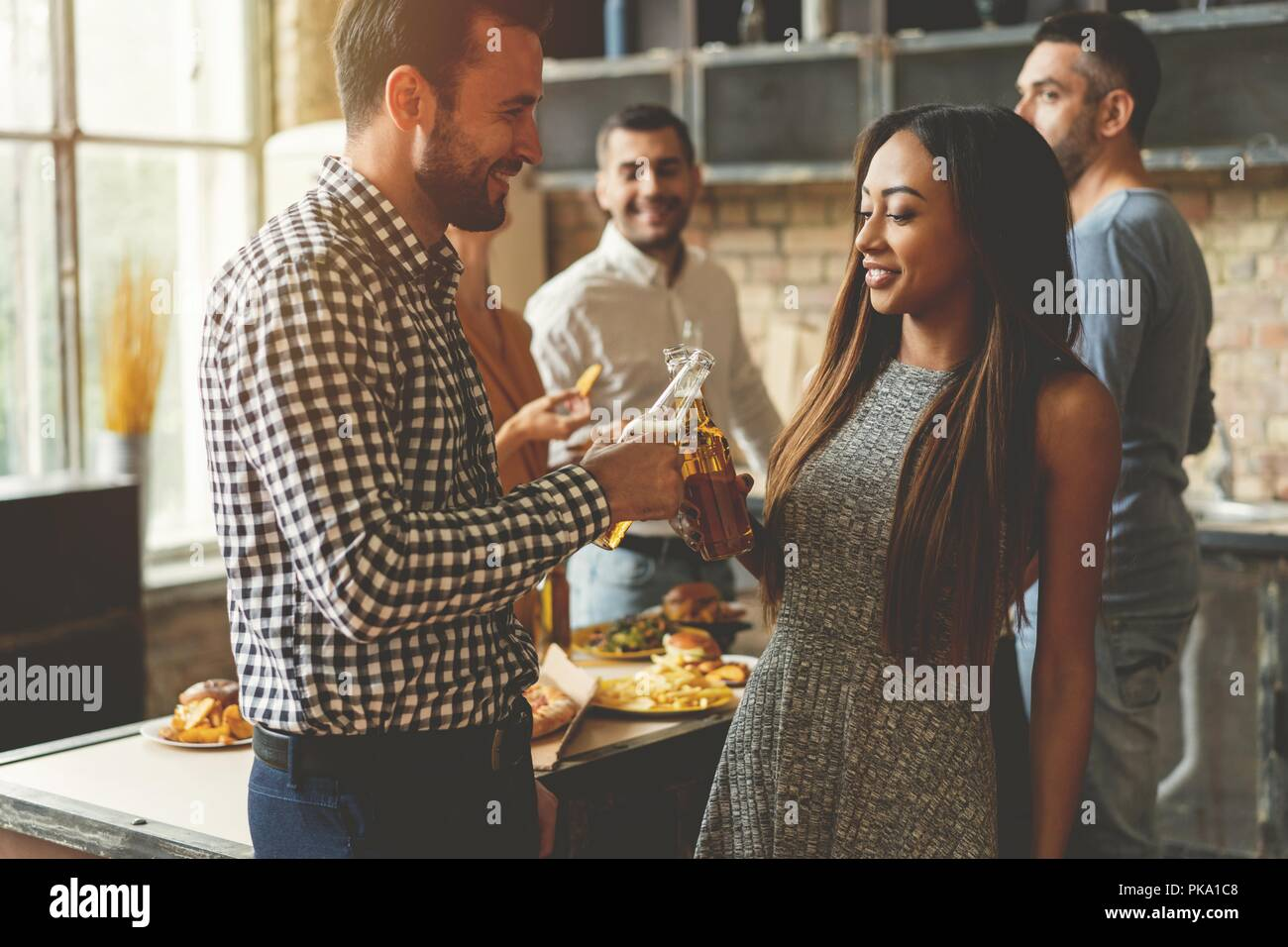 Party with best friends. Group of cheerful young people enjoying home party with snacks and drinks while communicating on the kitchen. - Stock Image