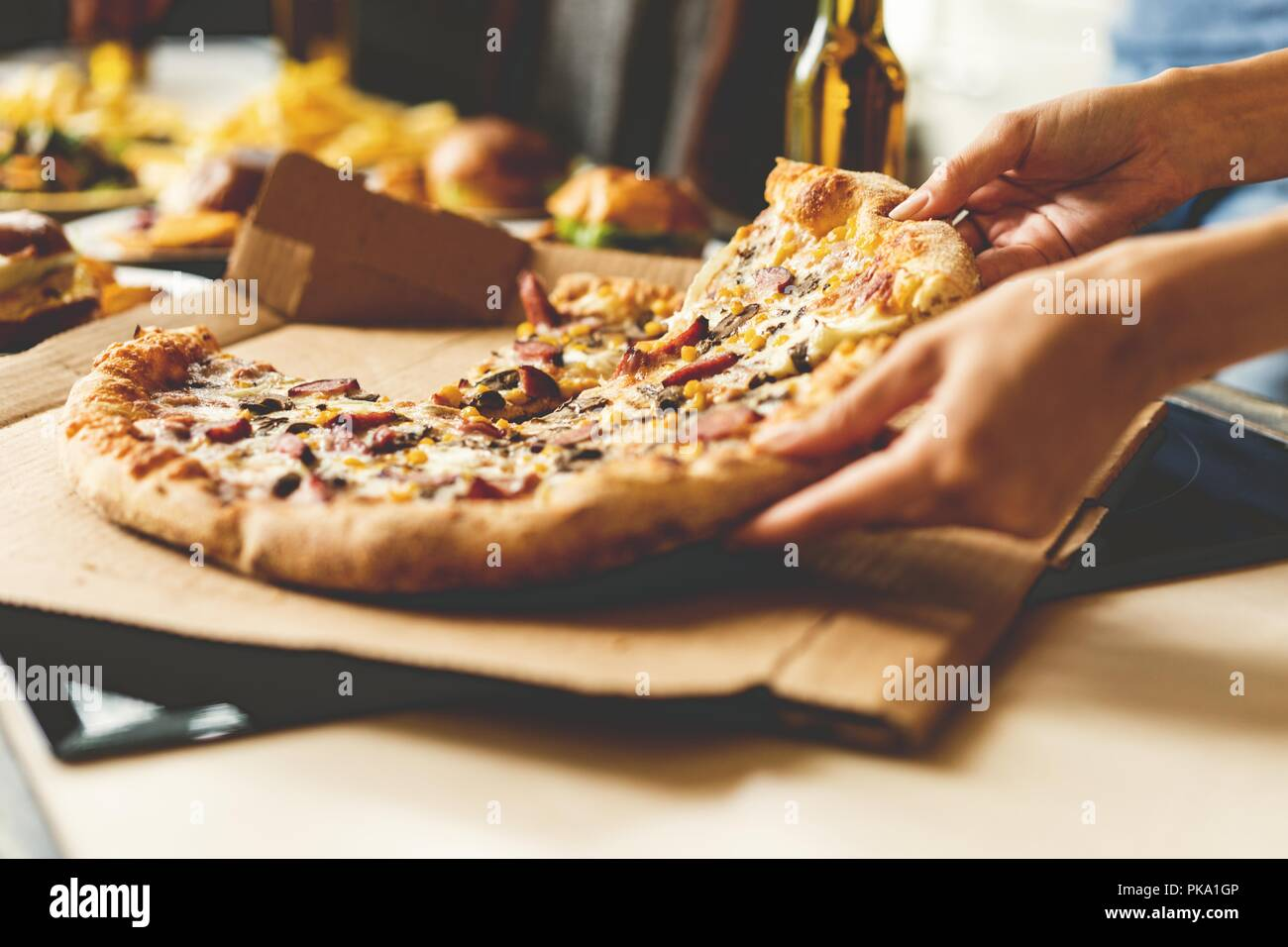 Friends taking slices of tasty pizza from plate, close up view. - Stock Image