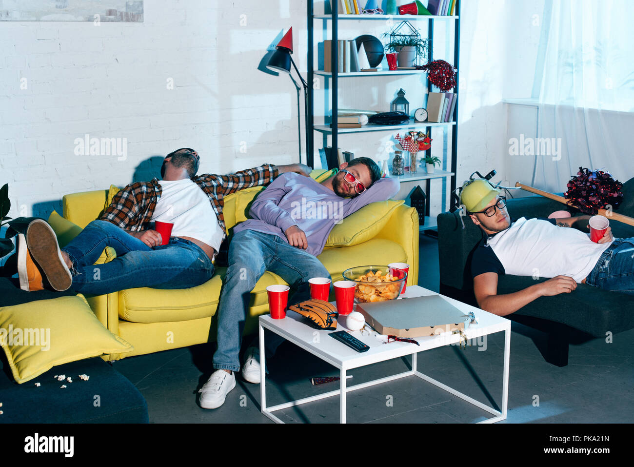 drunk young male friends sleeping on couches after home party - Stock Image