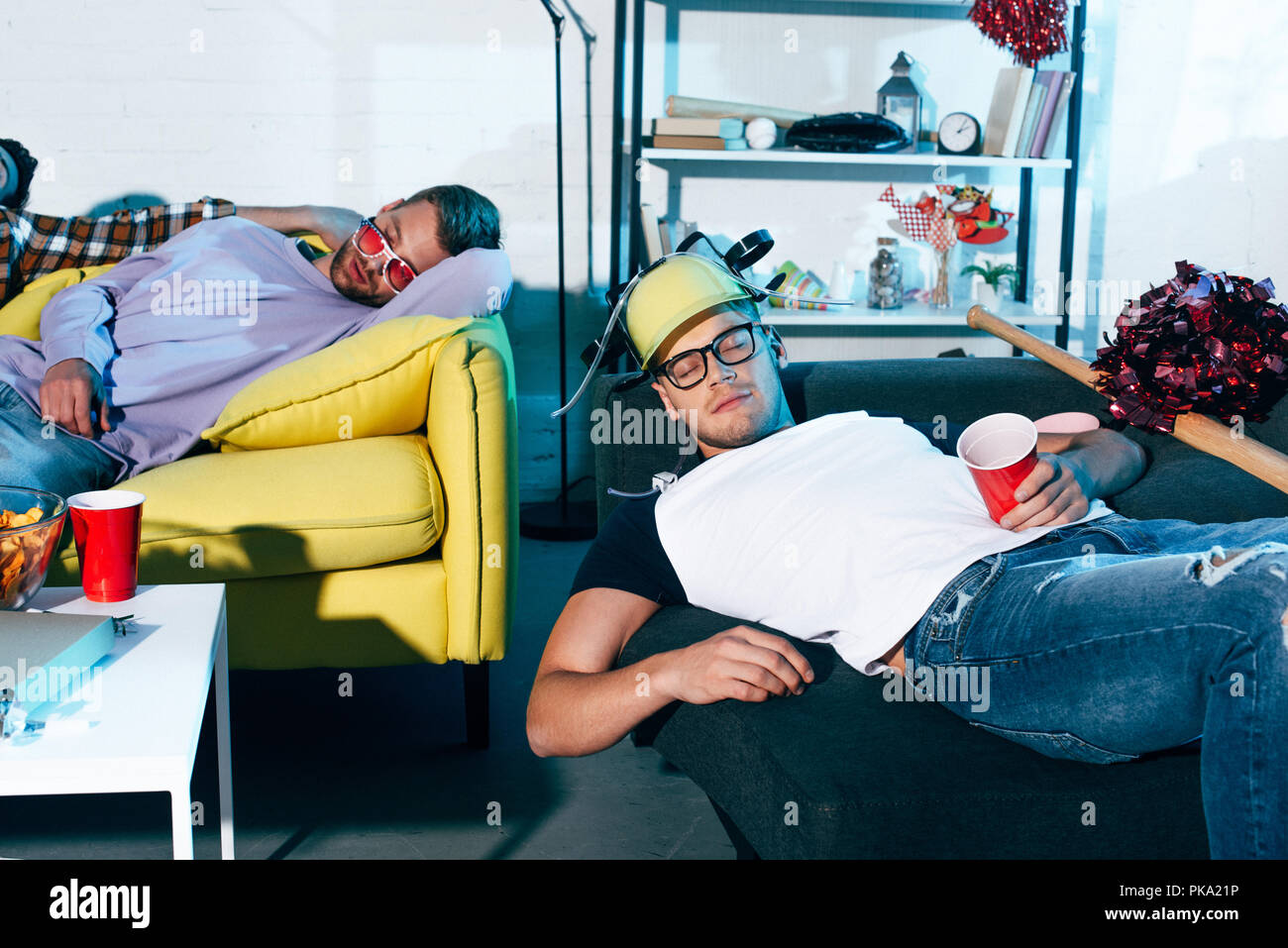 drunk young men sleeping on couches after home party - Stock Image