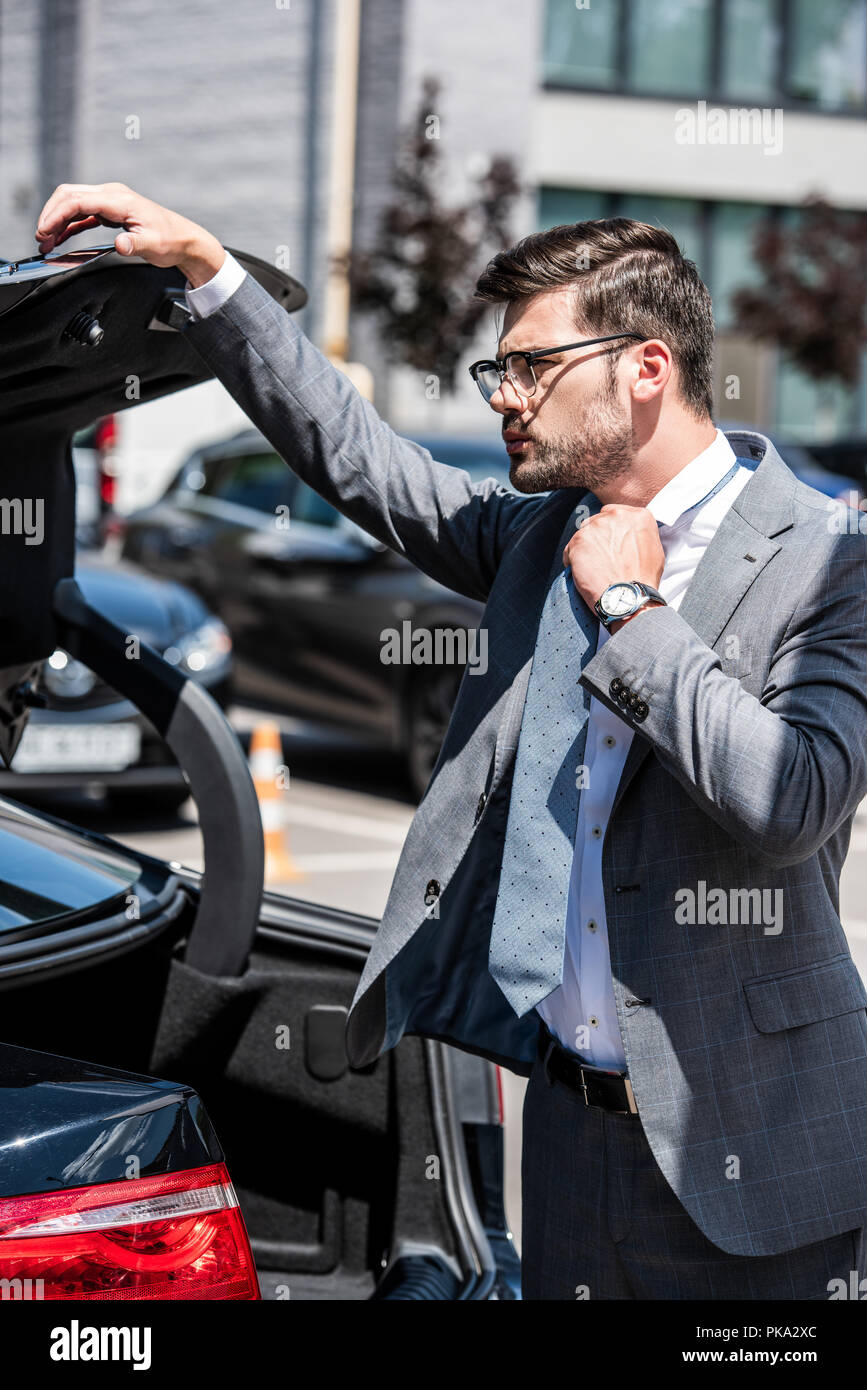 young businessman in eyeglasses closing car trunk at street - Stock Image