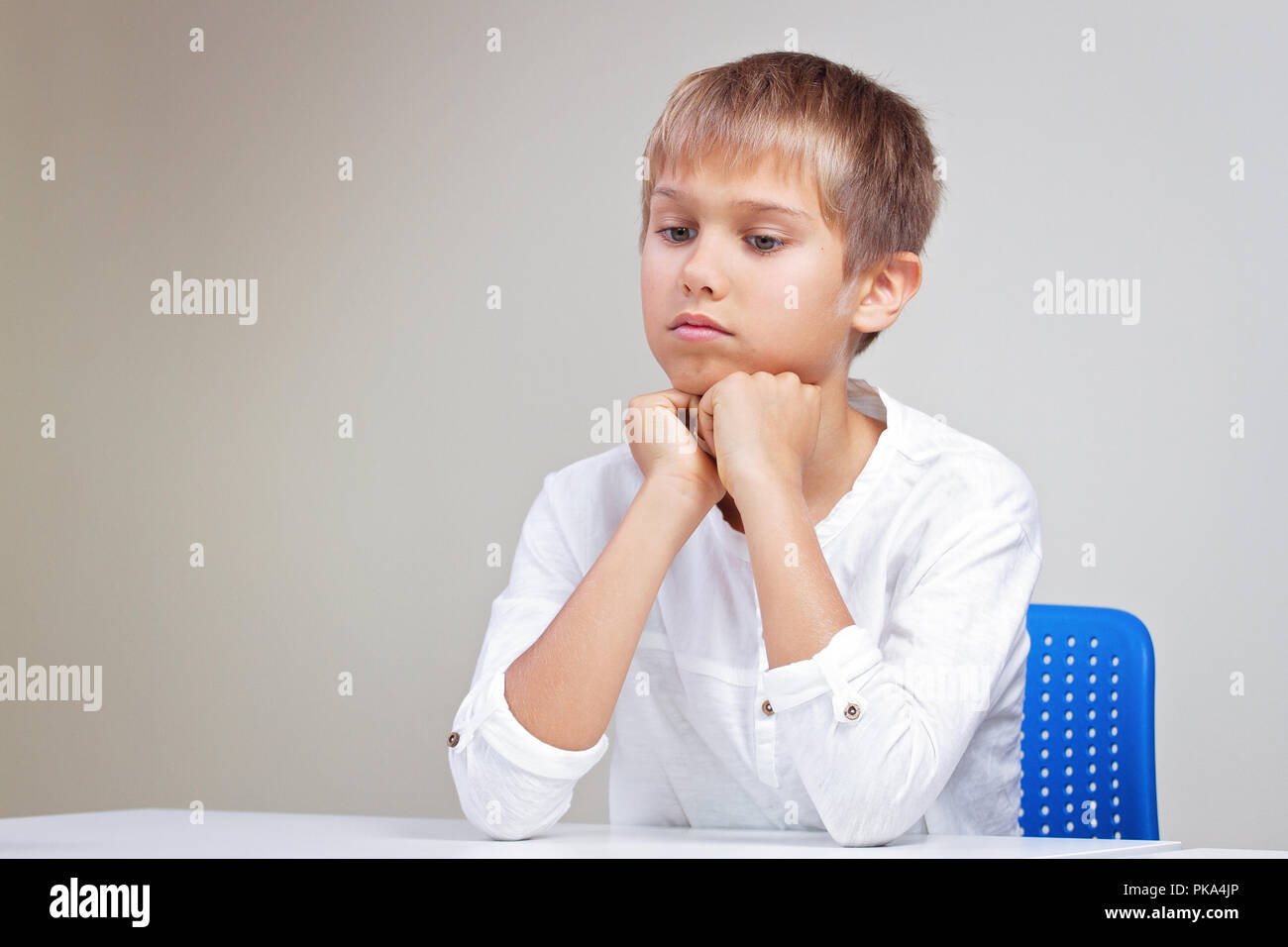 Thinking schoolchild sitting at empty white desk - Stock Image
