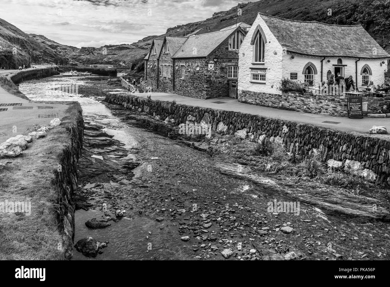 Tourists enjoy a brief respite from the persistent storms that pass over the picturesque little harbour at Boscastle on the North Cornish coast. - Stock Image