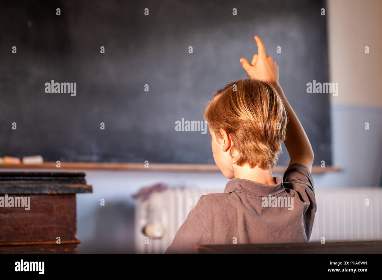 Concept of public primary school education with young boy raising his hand in the classroom. - Stock Image