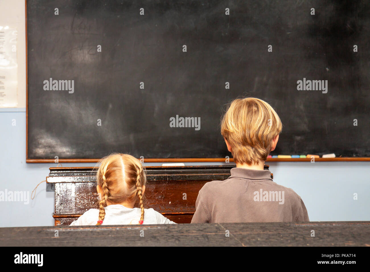 Concept of public primary school education with young boy and girl sitting in the classroom. - Stock Image