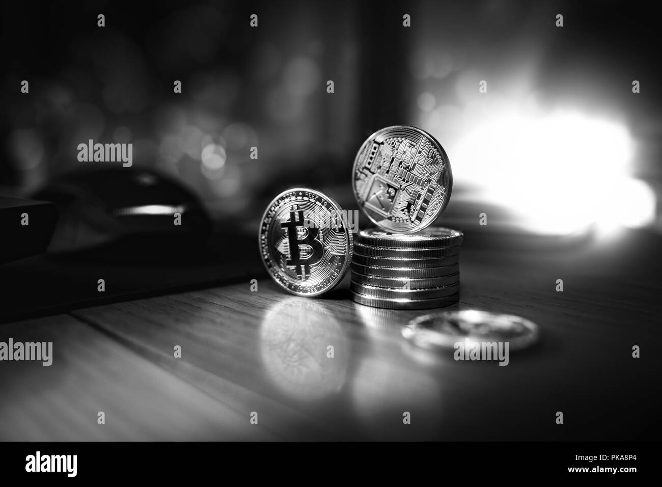 Bitcoin money lies on the wooden table and shine like a diamond in the darkness. - Stock Image
