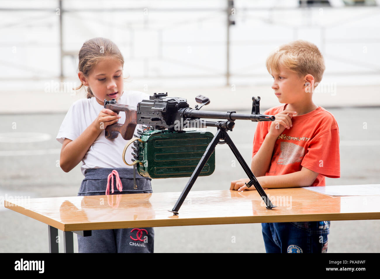 Russia, Vladivostok, 08/25/2018. Kids watch PK machine gun (known as 'Kalashnikov's Machinegun') on annual military exhibition 'Russian Army 2018'. - Stock Image