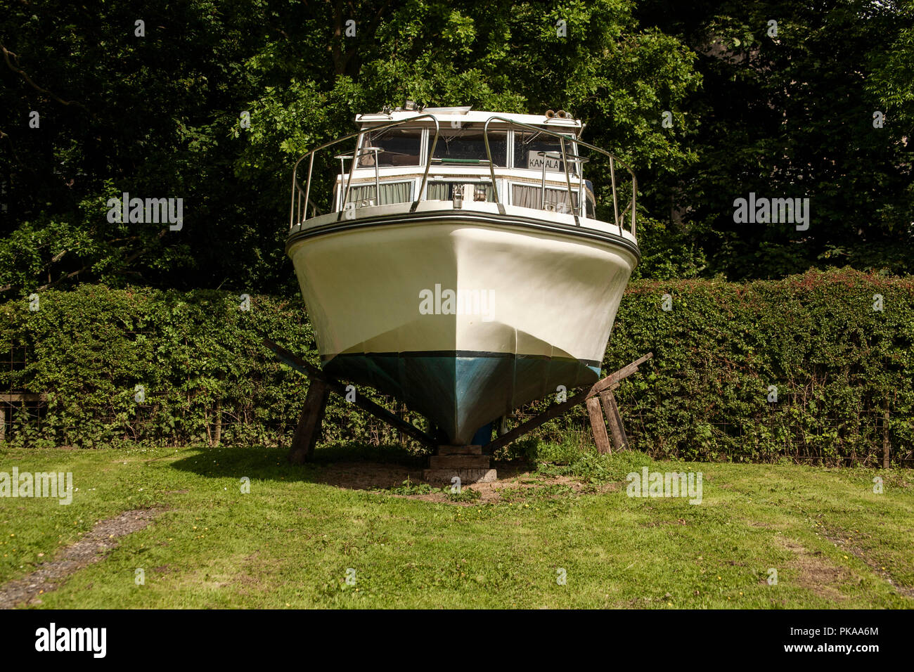 Front view of Cabin Cruiser mounted on supports out of water. Boat winterized boat winterized in dry dock - Stock Image