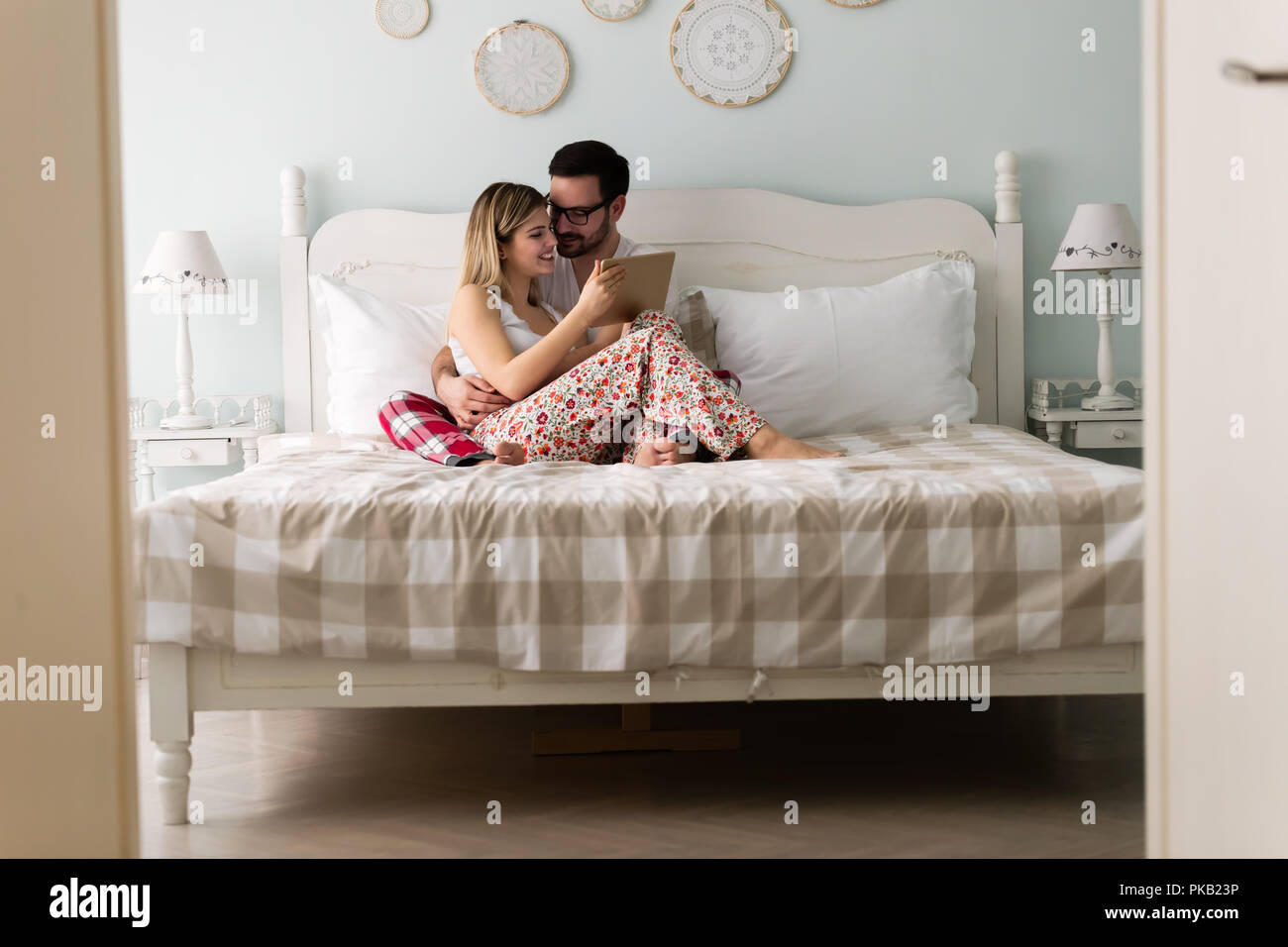 Young Attractive Couple Using Tablet In Bedroom Stock Photo Alamy
