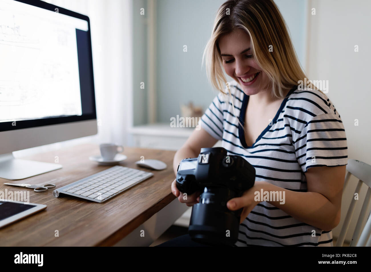 Portrait of young woman designing at home - Stock Image
