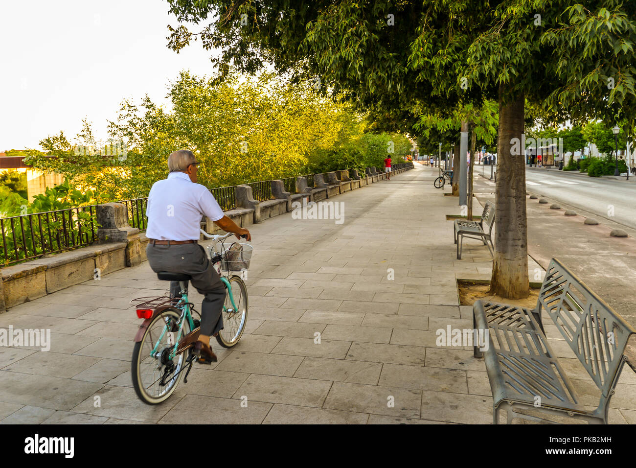 Cordoba/ Spain - 08/20/18 - A man biking along the river in the old town area of Cordoba - Spain - Stock Image