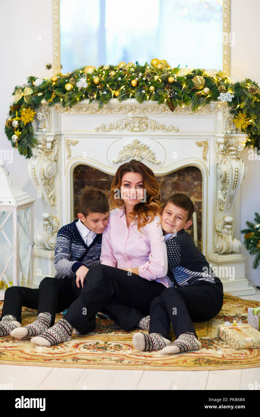 Young caucasian mother sitting with sonsnear deco rated fireplace. - Stock Image