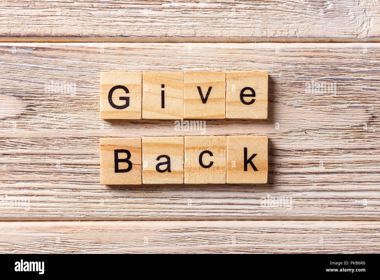 Give Back word written on wood block. Give Back text on table, concept. - Stock Image