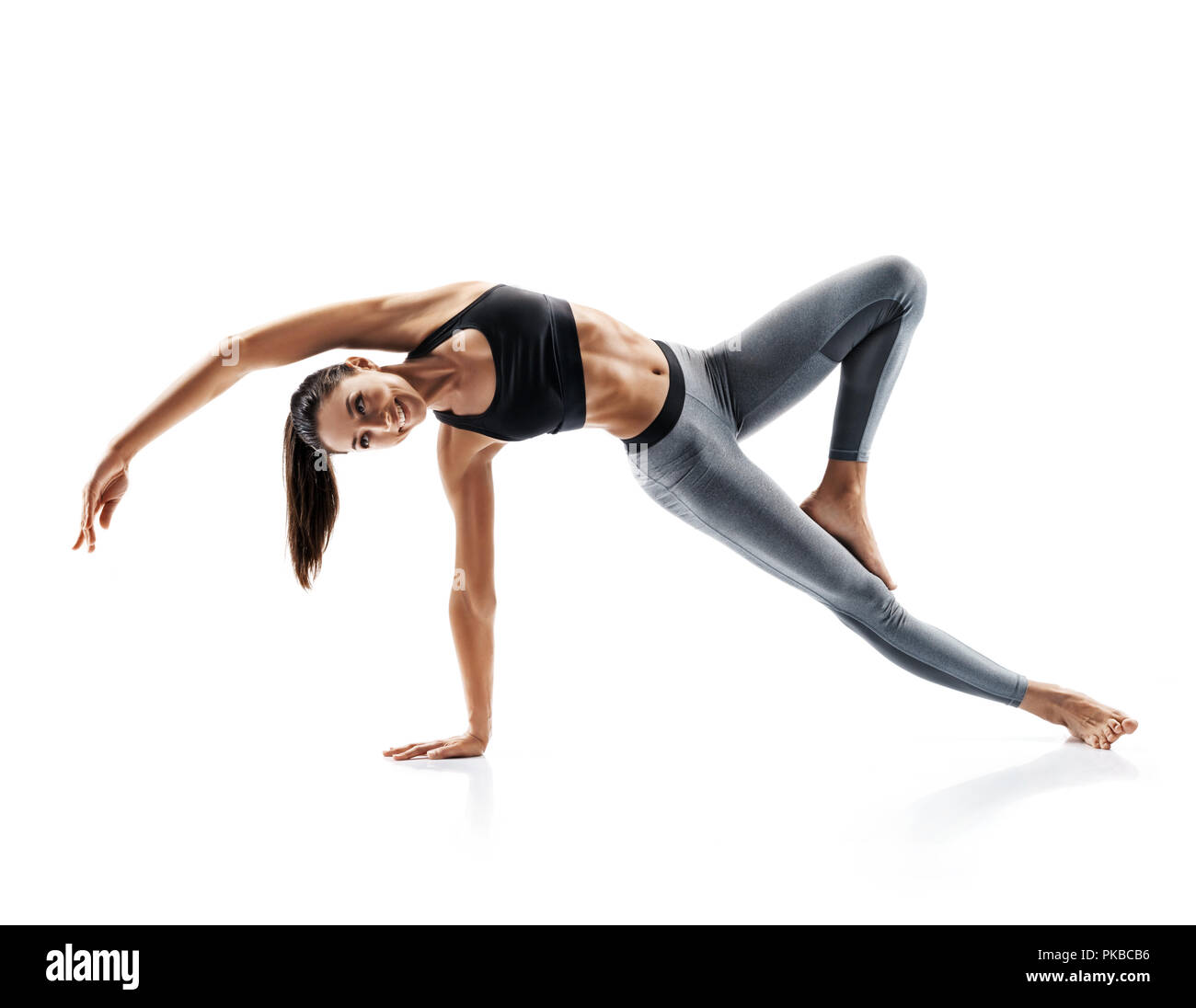 Young attractive girl practicing yoga isolated on white background. Concept of healthy life and natural balance between body and mental development. F - Stock Image
