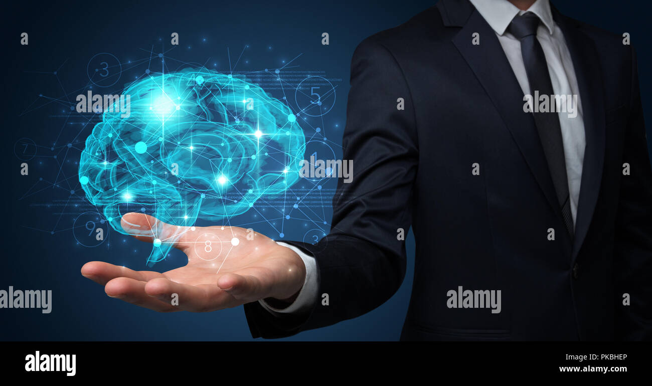 Businessman holding human brain on his hand with logistics symbols around - Stock Image