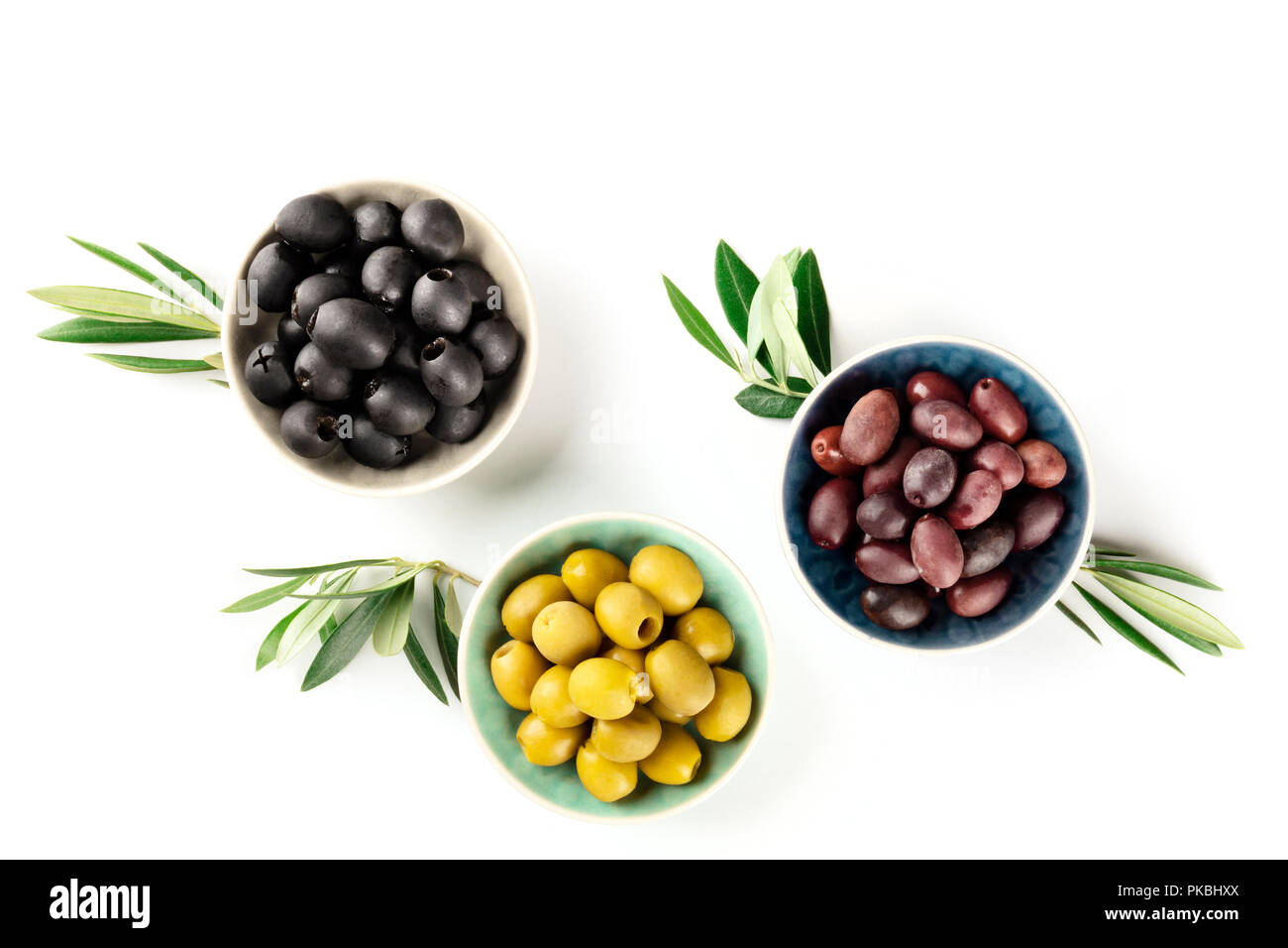 Overhead photo of various olives in bowls on white with copy space - Stock Image