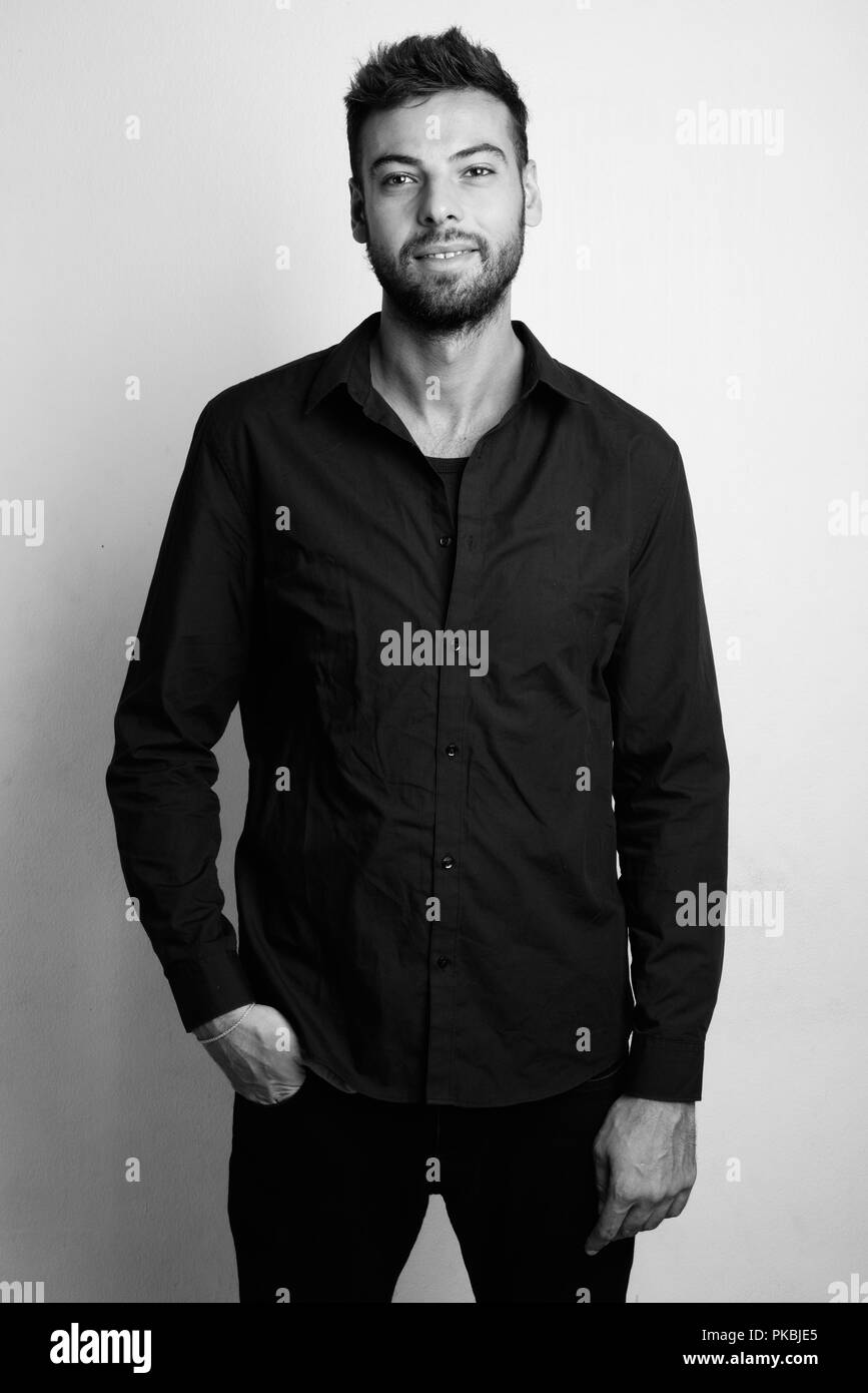 Young handsome bearded businessman in black and white - Stock Image