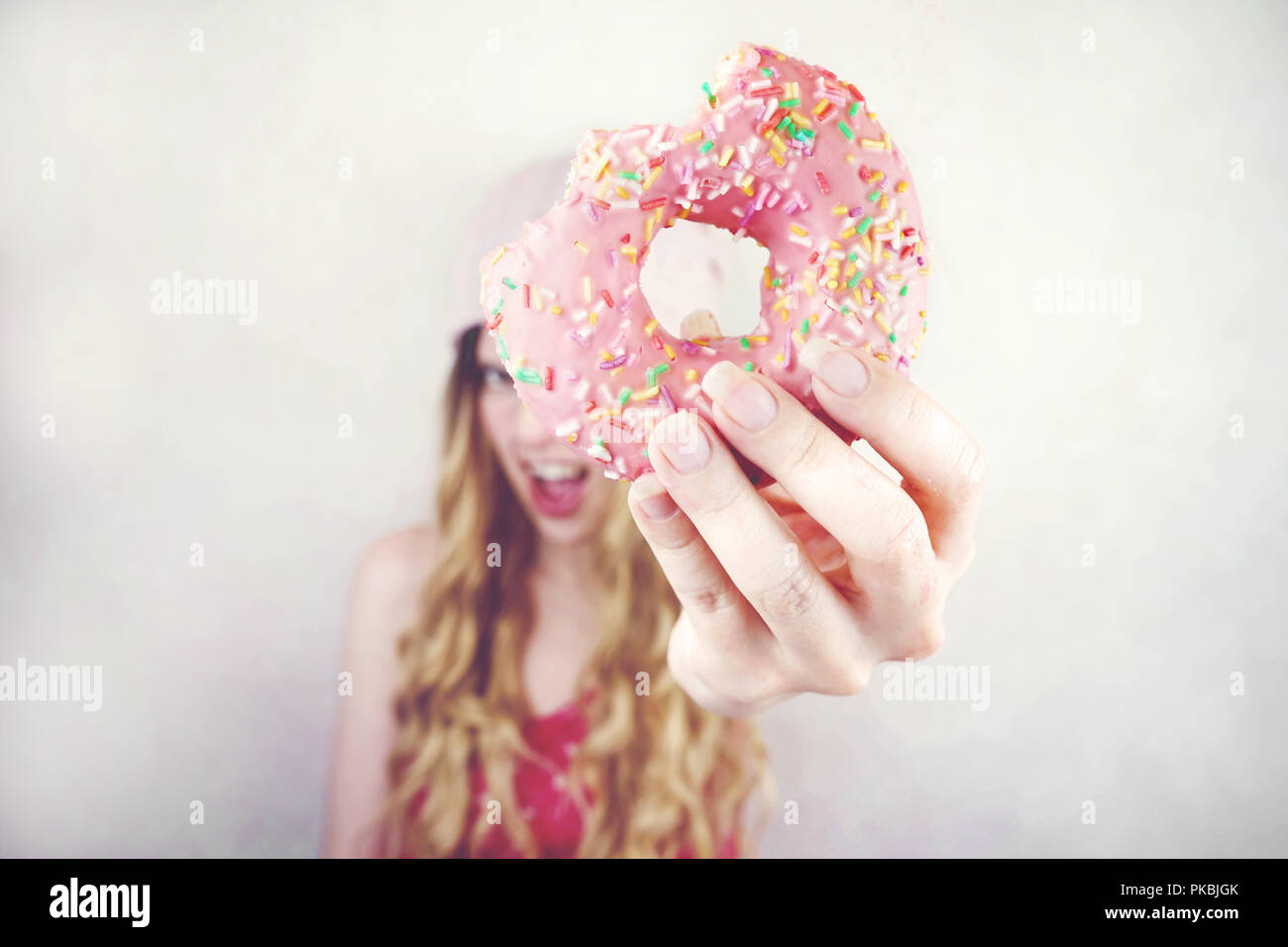 Portrait of a young and funny blonde woman eating a pink donut - Stock Image