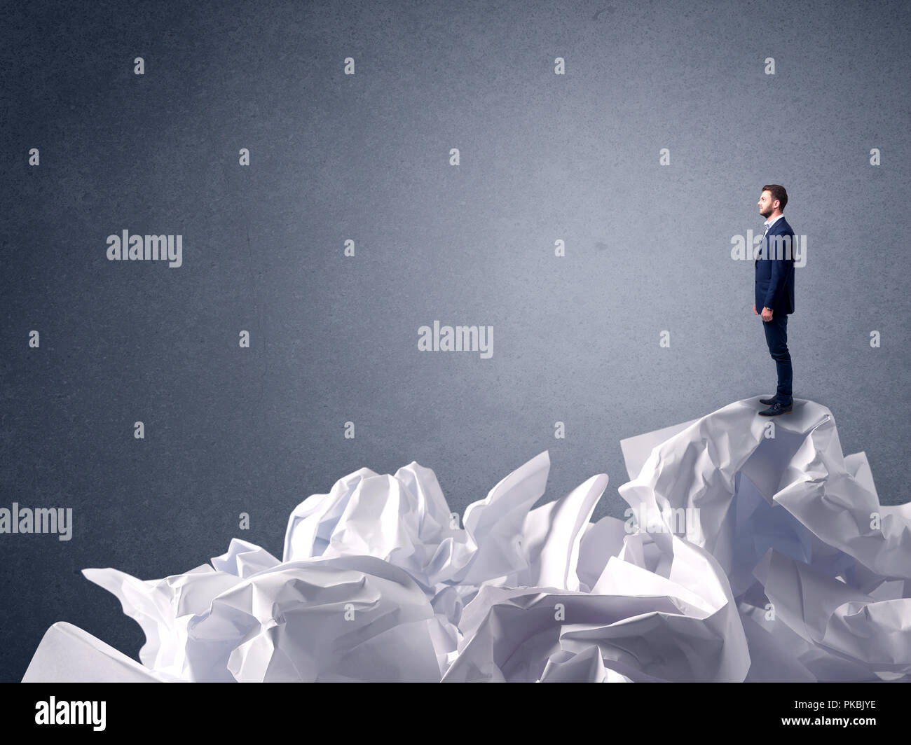 Thoughtful young businessman standing on a pile of crumpled paper  - Stock Image